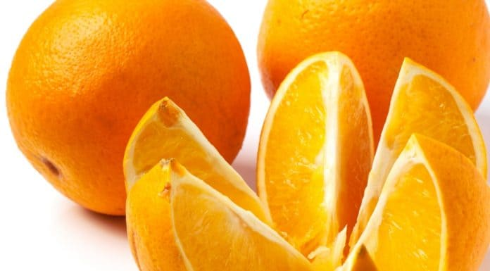 sliced and whole oranges over white