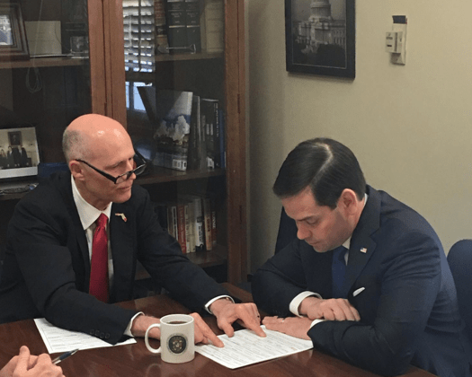 marco rubio and rick scott reviewing document 525x420